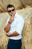 Young man good looks in sunglasses at the straw. The guy in the white shirt and sunglasses posing at the straw stack. Series stock images