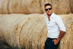 Young man good looks in sunglasses at the straw. The guy in the white shirt and sunglasses posing at the straw stack. Series royalty free stock photos