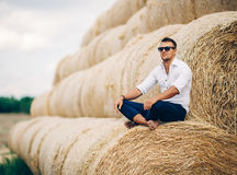 Young man good looks in sunglasses at the straw. The guy in the white shirt and sunglasses posing at the straw stack. Series royalty free stock images