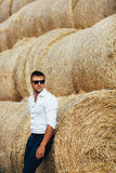 Young man good looks in sunglasses at the straw. The guy in the white shirt and sunglasses posing at the straw stack. Series Royalty Free Stock Image