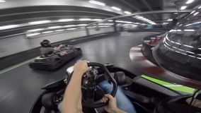 Young man gorgeous first person pov driving leisure go-cart car on karting lap race extreme sport action inside arena