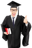 Young man in gown holding books and giving thumb up. Young man in graduation gown holding books and giving thumb up isolated on white background Royalty Free Stock Images