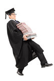 Young man in graduation gown carrying bunch of books. Full length portrait of young man in graduation gown carrying bunch of books isolated on white background Stock Photo