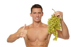 Young man with grapes Royalty Free Stock Image