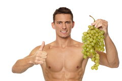 Young man with grapes Royalty Free Stock Photos