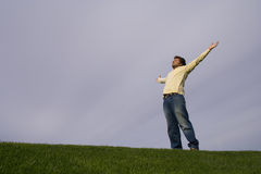 Young man in the grass. Looking to the sky with his arms outstretched Royalty Free Stock Photo