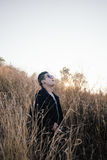 Young man in grass field with sunrise Royalty Free Stock Photo