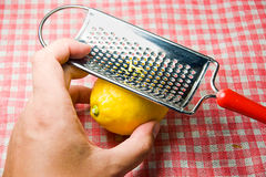 Young man grating fresh lemon Stock Image
