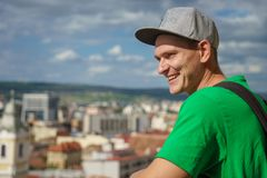 Young man in a gray baseball cap and green t-shirt on background of the city and blue sky with clouds.  stock photography