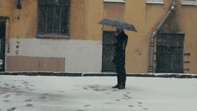 Man in coat with umbrella standing under snow sipping coffee from plastic cup. Young man in gray coat with black umbrella standing in middle of snowy courtyard stock video