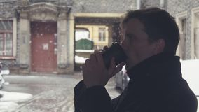 Close-up of young man drinking coffee from plastic cup on street under snowfall. Young man in gray coat and knitted scarf standing under canopy of building stock footage