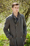 Young man in a gray coat. Stands on a background of trees Stock Photo