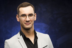 Man in a gray suit and glasses on a blue background. The young man in a gray suit and glasses on a blue background. Business portrait. Copy space Stock Photo