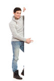 Young man in gray sweater holding banner. Handsome man in jeans and gray sweater holding banner. Full length studio shot isolated on white Royalty Free Stock Image