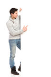 Young man in gray sweater pointing at banner. Handsome man in jeans and gray sweater pointing at banner. Full length studio shot isolated on white Stock Photos