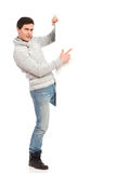 Young man in gray sweater pointing at a banner. Handsome man in jeans and gray sweater pointing at a banner. Full length studio shot isolated on white Stock Photo