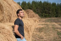 A young man in a gray t-shirt and jeans stands at a haystack, breathing clean air, freshness, rest after work, harvesting, concept. Young man in gray t-shirt and stock photos