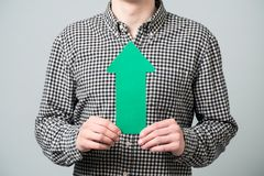 Young man with green arrow Stock Images