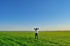 Young man on a green field Royalty Free Stock Image