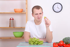 Young man with green grape in the kitchen Stock Photo