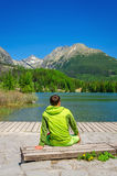 Young man in green jacket by clear mountain lake Royalty Free Stock Images
