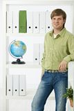 Young man in green office Stock Images