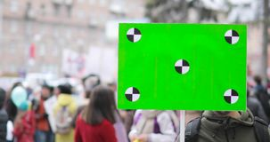 Young man with green screen poster in his hand on city demonstration.
