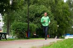 Young man in a green shirt and blue jeans running on summer park. Happy young man in a green shirt and blue jeans running on summer park Royalty Free Stock Photography