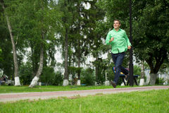 Young man in a green shirt and blue jeans running on summer park Royalty Free Stock Photos