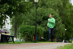 Young man in a green shirt and blue jeans running on summer park Stock Photos