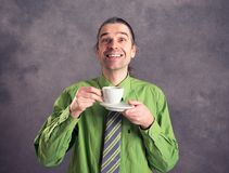 Young man in green shirt and necktie with cup of coffee Royalty Free Stock Photography