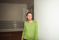 Young man in green shirt, standing at wall and looking forward Stock Photography
