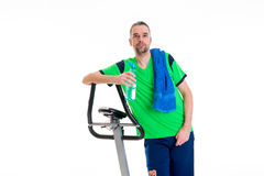 Young manwith water bottle train with fitness machine. Young man in green shirt with water bottle train with fitness machine royalty free stock images