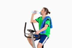 Young manwith water bottle train with fitness machine. Young man in green shirt with water bottle train with fitness machine royalty free stock photos