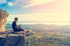 Young man in green sportswear is sitting on cliff's edge. And looking to misty valley bellow royalty free stock photo