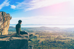 Young man in green sportswear is sitting on cliff's edge. And looking to misty valley bellow with Vintage tone stock images
