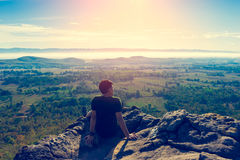 Young man in green sportswear is sitting on cliff's edge. And looking to misty valley bellow with Vintage tone royalty free stock photos