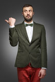 Young man in a green suit, shows left Stock Images