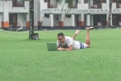 Young man in the green tropical park working online with laptop. Freelancer man on Bali island concept. stock photos