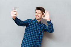 Young man greeting with somebody while making videocall or selfie. Young man greeting with somebody while making video call or selfie on smartphone stock photos