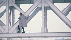 Young man in a grey coat climb on the bridge span. On a windy day stock video footage
