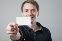 Young man on grey. Young man showing white empty paper card on grey background Stock Photo