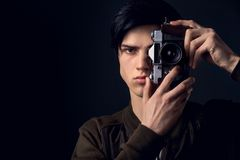 Young man  on a grey wall studio concept taking photos. Looking camera close-up concentrated on a good shot Stock Photo