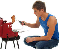 Young man grilling chiken Stock Photography