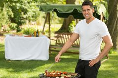 Young man grilling Royalty Free Stock Photos