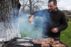 Young man grilling pork and fish Royalty Free Stock Photography