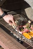 Hand of young man grilling some meat and vegetable royalty free stock photo