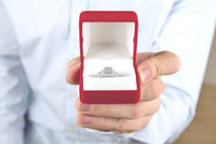 Engagement / marriage / wedding proposal scene. Close up of man handing the expensive gold platinum diamond ring to his bride. royalty free stock image