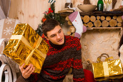 Young man guessing at his Christmas gift Stock Image