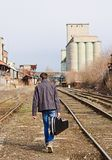 Young man with guitar case in hand going away by rails. Rear view Royalty Free Stock Images